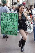 NEW YORK - SEPT 17: A protester holds a whip and a sign that reads 'Naughty Bankers Need A Spanking'