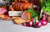 stock photo of smoked ham  - smoked meat and sausages on a linen cloth - JPG