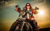 stock photo of biker  - Biker girl with sunglasses sitting on motorcycle - JPG