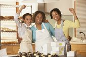 Portrait of three woman cheering while working in bakery