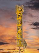 Vintage neon garage arrow sign with sunset sky.
