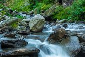 Cascade of Bhagsu waterfall in Himalayas. Bhagsu, Himachal Pradesh, India. Polarizer filter used