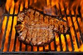 A steak flame broiled on a barbecue, shallow depth of field.