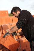 Mason making adjustments to brick
