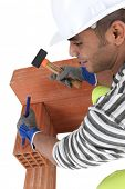 stock photo of gad  - Mason chiseling brick - JPG