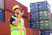 young harbor worker talking on the walkie-talkie at container warehouse
