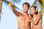Couple on beach happy in swimwear, man pointing showing and looking at view. Beautiful young multi-e