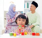 Malay girl building a wooden toy house. Southeast Asian family at home. Muslim parents and child liv