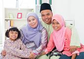 Happy Asian family at home. Muslim family having fun indoors. Southeast Asian parents and children smiling.