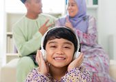 Muslim girl listening to song at home. Southeast Asian family living lifestyle. Happy smiling Malay