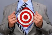 Businessman in classic superman pose tearing his shirt open to reveal target symbol on chest concept