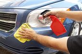 image of headlight  - Hand applying instant spray wax on car fender - JPG