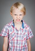 stock photo of misbehaving  - A frustrated and angry looking young boy pulling a face - JPG