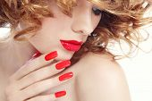 Close-up portrait of young beautiful woman with stylish manicure and red lipstick, selective focus