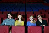 Four young happy friends sit on seats in cinema theater and see movie.
