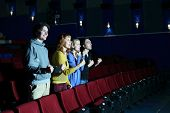 Four happy friends stand, look at screen and cheer in cinema theater. Focus on left pair.