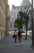 Young Couple Is Walking Near Parliament In Budapest, Hungary.
