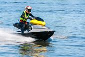 image of jet-ski  - Young woman riding her jet ski on water - JPG