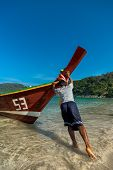 PHUKET, THAILAND JANUARY 3: Thai longtail boat fisherman pushes on January 3, 2014 in Phuket, Thaila