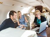 Businesswoman pointing at laptop to colleagues while discussing in private jet