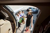 Full length of rich woman with shopping bags boarding private jet while pilot and airhostess looking