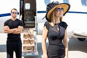 stock photo of diva  - Happy woman wearing sunhat and sunglasses with bodyguard and private jet in background - JPG