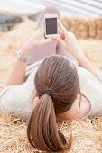 foto of haystacks  - Beautiful young girl lying on haystacks and using a mobile phone - JPG