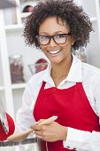 A beautiful mixed race African American girl or young woman looking happy wearing geek glasses a red