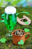 Glass of green beer, pitcher with coins and horseshoe on grass close-up