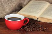Cup of coffee with coffee beans and book on wooden table on sackcloth background
