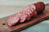 pic of deer meat  - Sliced salami on wooden cutting board closeup - JPG