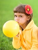 Little Girl Is Inflating Yellow Balloon