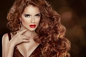 Long Curly Red Hair. Beautiful Fashion Woman Portrait. Beauty Model Girl With Luxurious Glossy Hair,