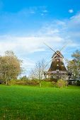 stock photo of wind vanes  - Traditional wooden windmill in a lush garden with four sails or blades turning in the wind to generate power and energy for farming or manufacture from the kinetic energy of the wind - JPG