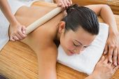 Smiling brunette getting a herbal compress massage at the health spa