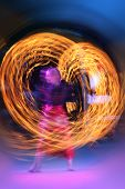 image of poi  - Artist juggling with two burning poi - JPG