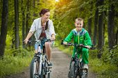 Happy family. mother and son riding bicycle in the park