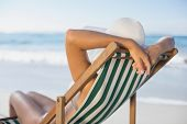 Slim woman relaxing in deck chair on the beach on a sunny day