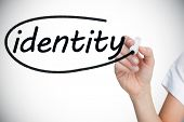 Businesswoman writing the word identity against white background with vignette