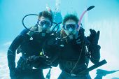 Friends on scuba training submerged in swimming pool looking to camera on their holidays