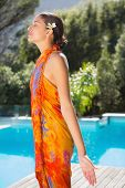 Brunette in sarong standing with arms out by the pool outside at the spa