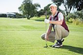 Confident golfer kneeling holding his golf club on a sunny day at the golf course