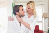 Cute couple in bathrobes spending time together at home in the living room