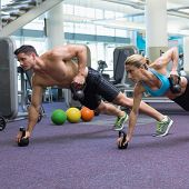 Bodybuilding man and woman lifting kettlebells in plank position at the gym