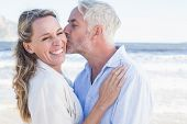 Man kissing his smiling partner on the cheek at the beach on a sunny day