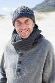 Attractive man smiling at camera on the beach in hat and scarf on a bright but cool day