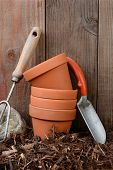 Closeup of garden tools and flower pots against a wooden backyard fence.