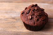 foto of chocolate muffin  - Chocolate muffin and coffee grains on wooden background - JPG