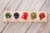 stock photo of diagonal lines  - View from above of a line of assorted cured savory olives and peppers in individual taster plates on a wooden board on a wood table with diagonal planks centered with copyspace - JPG