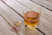 picture of tumbler  - Tumbler of whiskey and tip of loose coins standing on an old rustic wooden bar counter with diagonal planks and copyspace high angle view - JPG